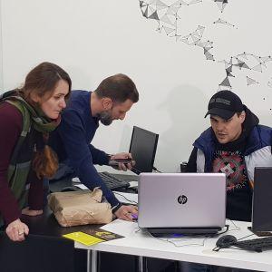 En grupp unga personer står lutade över ett arbetsbord och diskuterar.