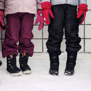 Fyra barn står och köar ute på gården