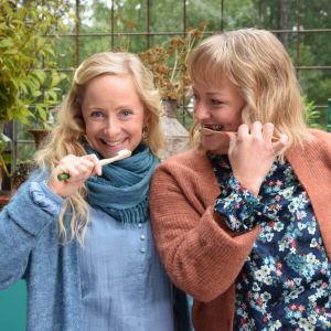 Strömsös programledare Alexandra De Paoli och Elin Skagersten-Ström står med varsin tandborste och tittar leende in i kameran.