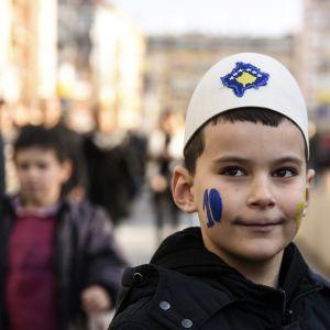 Pojke i Kosovo i traditionell albansk mössa med Kosovos flagga påsydd.