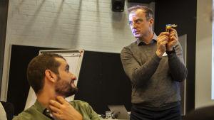 En man i grå tröja förevisar lego för andra vuxna män.