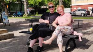 Två glada kvinnor sitter på en bänk i solen.
