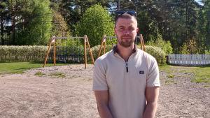 En man står på en solig skolgård.