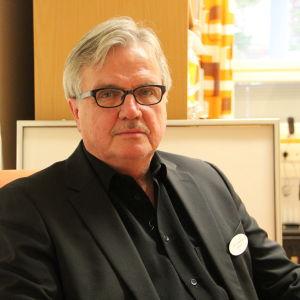 Mies, Juha Hänninen katsoo kameraan.