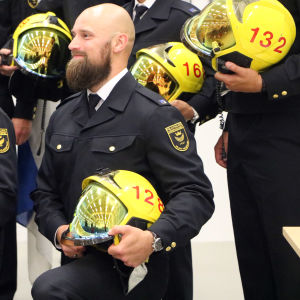 Brandmännen står på knä och poserar.