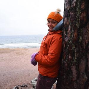Ilse Klockars iklädd orange jacka tittar in i kameran och ler. Hon lutar mot en tall vid sandstranden i Hangö.