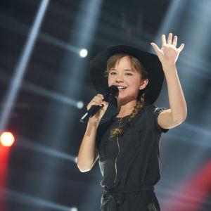 Sofie på MGP-scenen med svart hatt.