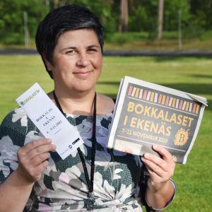 Lotta Lerviks står utomhus och håller i två Bokkalaset-broschyrer.