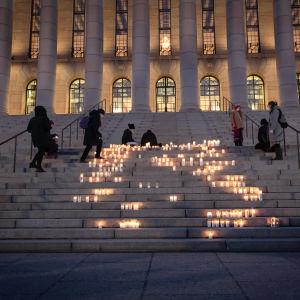 Ljuslyktor tänds i kvällsmörkret på riksdagshusets trappa.