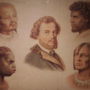 En gammal skolplansch som visar olika raser i form av porträtt. DEn vite mannen i mitten, andra raser runt omkring.