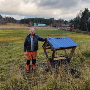 En man står och lutar mot en matkoja för djur på en stor åker.