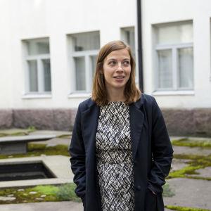 Undervisningsminister Li Andersson står utomhus i en stenträdgård. I bakgrunden syns ett vitt stenhus.