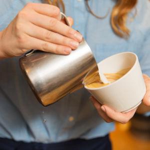 En kvinna håller i en kaffekopp och en kanna med skummad mjölk.