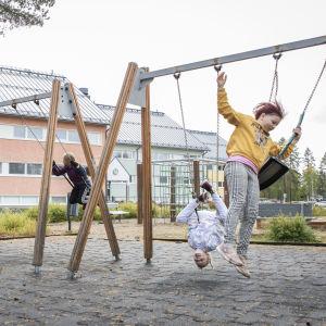 Lapsia kiikkumassa koulun pihalla.