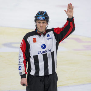 Jääkiekkoerotuomari Anssi Salonen nostaa kätensä ylös.