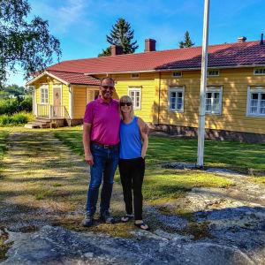 En kvinna och en man står framför ett gammal gult trähus.