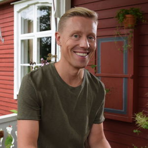 Nicke Aldén istuu punaisen talon edessä ja hymyilee kameraan.