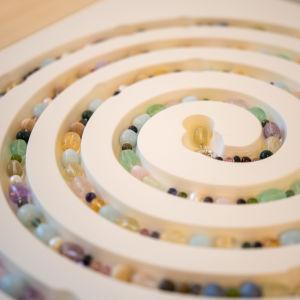 Ett konstverk av Kirsti Doukas och Kristian Saarikorpi med en kedja pärlor färggranna i ett spiralformat kärl.