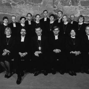 Helsingin Tuomiokirkon kryptassa 15 nuorta pappisvihkimyskandidaattia seisoo ja heidän edessää istuu 8 Tuomiokapitulin jäsentä