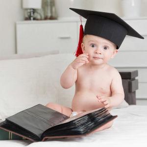 En baby i blöja sitter framför en bok med en svart hatt på huvudet. Hatten har en svart platta på sig och från den hänger en röd tofs ner på sidan. Babyn tittar in i kameran med stora ögon och har sin högra hand vid kinden.