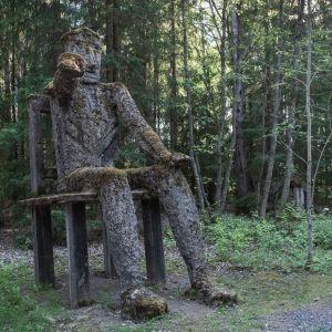 Iso veistos joka istuu tuolilla ja osoittaa toisella kädellä