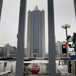 Gazpromin pilvenpiirtäjä kuvattuna pilvisenä talvipäivänä metalliraidan raosta.