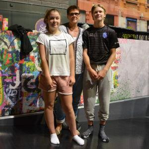 En äldre kvinnlig lärare står mellan två elever i 15-års åldern i ett aktivitetscenter med graffiti i bakgrunden.