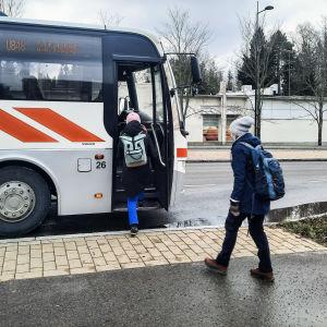Två passagerare stiger på en buss.