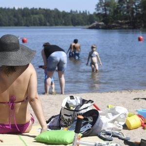 En kvinna sitter på en badstrand i bikini och hatt, i bakgrunden simmar barn och vuxna.
