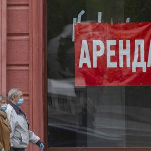 Man och kvinna som bär munskydd promenerar på gata vid skyltfönster med röd skylt där det står ''uthyres'' på ryska.