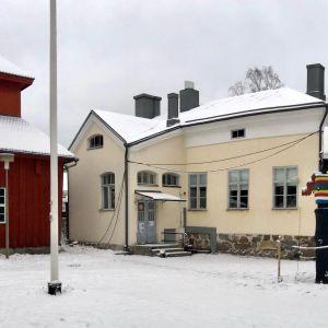 Talvinen pihapiiri jossa punainen puurakennus ja keltainen kivirakennus.