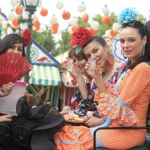 Flamencoasuihin pukeutuneet naiset juhlivat Feriaa Sevillassa.