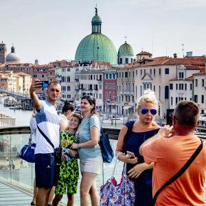 Turistit ottavat selfieitä Venetsiassa.