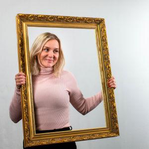 Märta Westerlund håller i tom tavelram och tittar igenom den medan Simon Karlsson fotograferar henne.