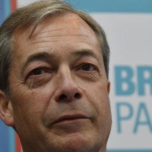 """Nigel Farage framför en skylt med texten """"Brexit Party""""."""