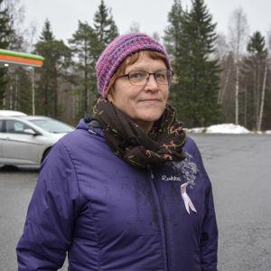 Kvinna står på parkering, tittar in i kameran och ler.