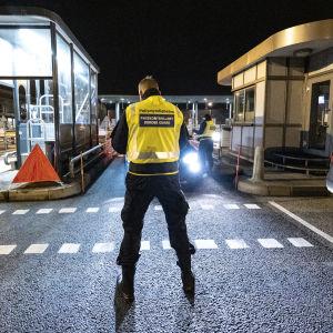 Gränspolis i reflexväst står mitt i bilden med ryggen mot kameran, i strålkastarljus från bil vid gränskontroll.