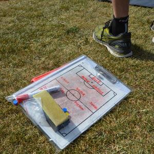 En taktiktavla för fotboll ligger på en gräsmatta.