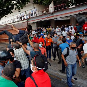 Ihmistä nostetaan kuorma-auton lavalle, ympärillä ihmisjoukko