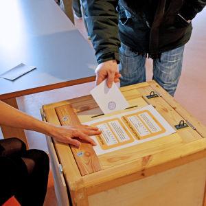 Väljare lägger valsedel i låda