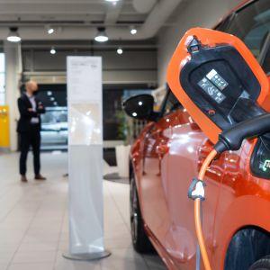 En orange elbil i en bilaffär laddas.