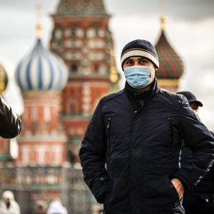 Två män står på Röda torget i Moskva med Vasilijkatedralens lökuloler i bakgrunden. Den ena mannen bär munskydd, den andra tar på sig munskydd.