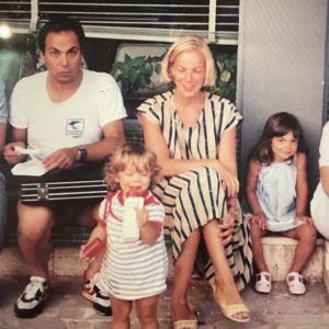 """Ryhmäkuvassa rakennuksen seinustalla istumassa vasemmalta Arto Bryggare, Carmelo """"Carlo"""" Bosco, Carla Bosco, äiti Anni Kirvesniemi-Bosco, Manuela Bosco pikkutyttönä ja Annin pikkuserkku Pia."""