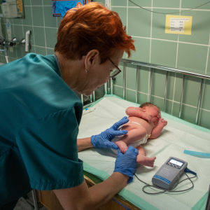 Barnmorskan Mervi Lanu mäter nyfödda Ronjas puls. Ronja ligger med blöja på skötbordet.