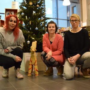 Tre kvinnor sitter på huk framför en pyntad julgran i Kimitos bibliotek.