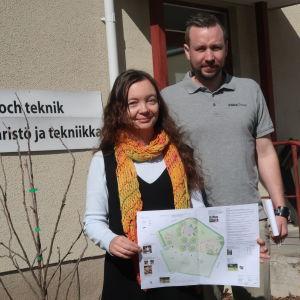 en kvinna och en man intill ett litet äppelträd framför en gul stenbyggnad med skylten miljö- och teknik