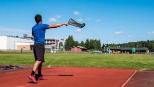 En man kastar en stövel vid en idrottsplan.