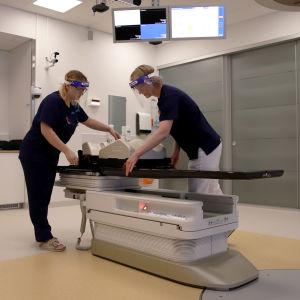 Röntgenhoitajat sädehoitolaitteen äärellä