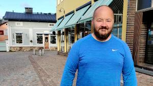 En man i blå skjorta står på Krämaregatan i Gamla stan i Borgå.