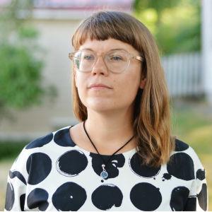 En kvinna med panlugg och svartvit klänning. Hon har på sig ett par ljusa glasögon och har axellångt hår. Bakgrunden är suddig men det syns träd och hus.